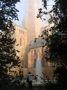 Photo of Speyer Cathedral with fountain in foreground on a foggy morning.