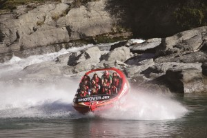 The image shows a jetboat doing a 360 degree turn on the Shotover River