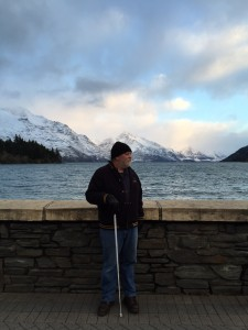 "The photo shows Greg on the shore of Lake Wakatipu at Queenstown with the mountain range ""The Remarkables"" in the background"
